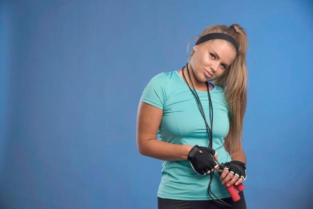 Młoda kobieta sprawny trzymając skakanki na szyi i uśmiechnięty.