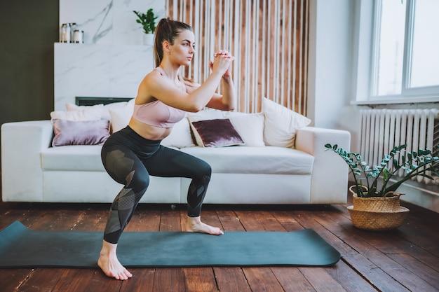 Młoda kobieta sprawny w odzieży sportowej robić przysiady w pomieszczeniu w salonie.