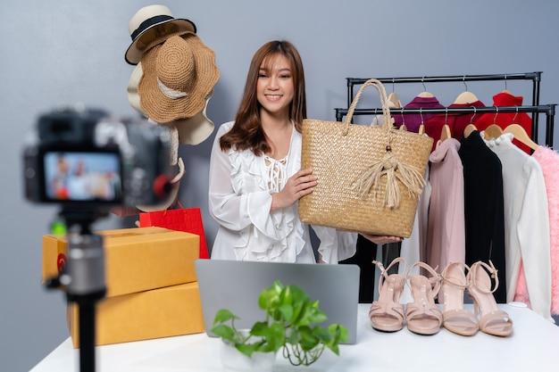 Młoda kobieta sprzedaje torby i ubrania online za pomocą transmisji na żywo z kamery, biznesowy e-commerce w domu