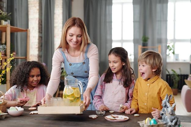 Młoda kobieta stawia na stole tacę z lemoniadą i częstuje dzieci napojem i ciastkami