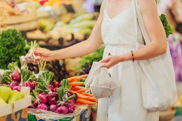 Młoda kobieta stawia owoce i warzywa w bawełnianej torbie na rynku żywności. ekologiczna torba wielokrotnego użytku na zakupy. koncepcja zero odpadów.
