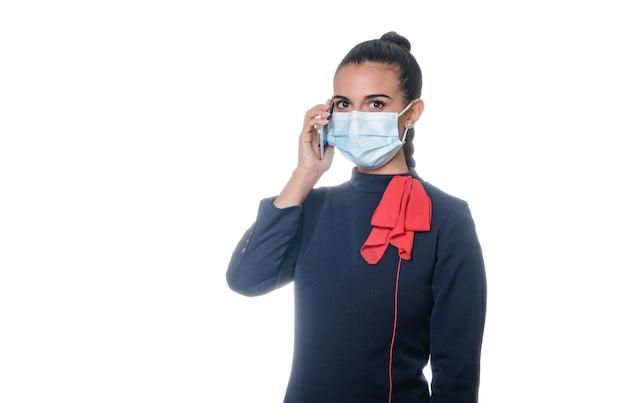 Młoda kobieta stewardessa powietrzna rozmawia przez telefon w masce na twarz, aby zapobiec pandemii koronawirusa