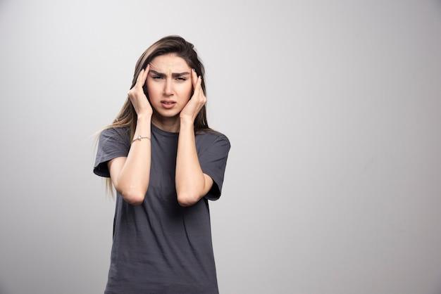 Młoda kobieta stoi i dotyka bólu głowy