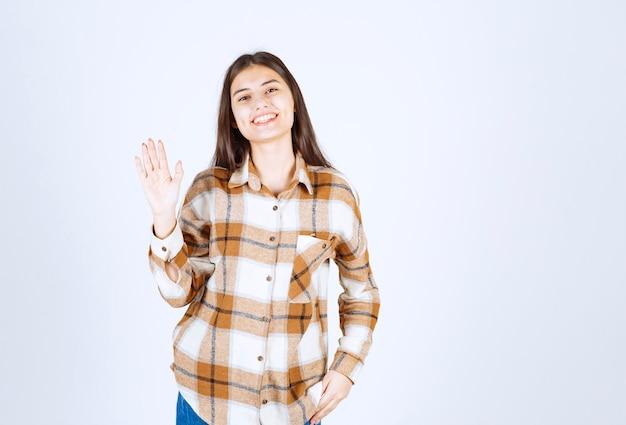 Młoda kobieta stoi i mówi cześć