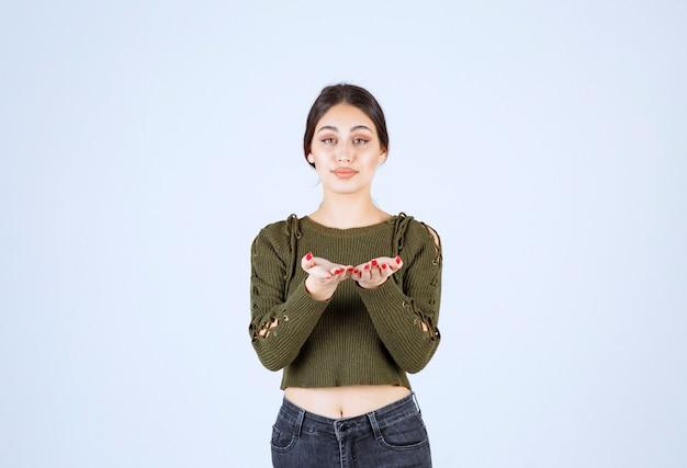 Młoda kobieta stoi i pokazuje jej ręce do kamery.