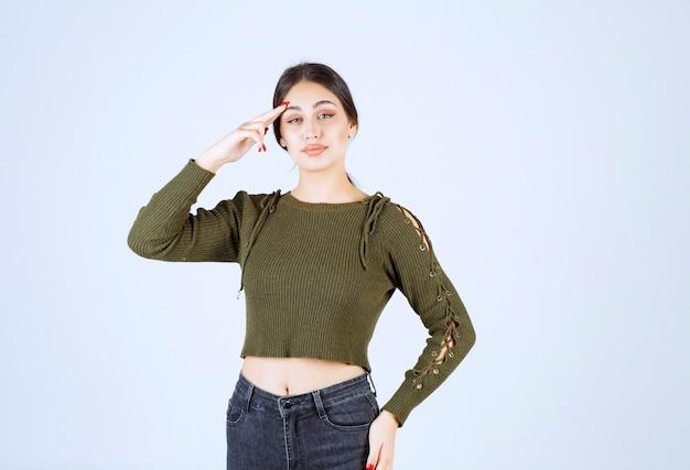 Młoda kobieta stoi i wskazuje na jej głowę na białym tle.