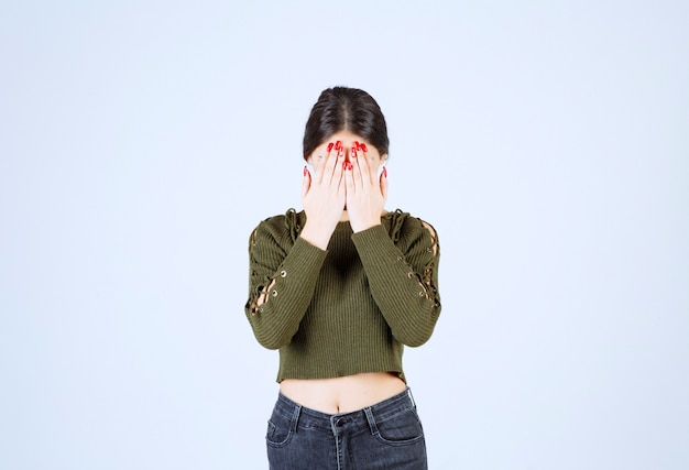 Młoda kobieta stoi i zakrywa jej twarz na białym tle.