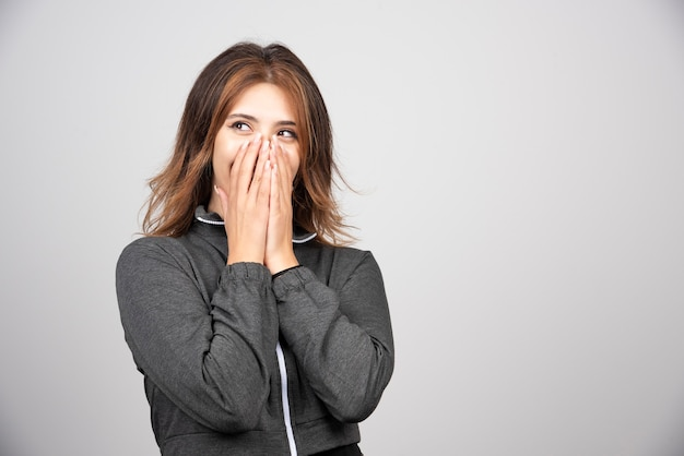 Młoda kobieta stoi i zakrywa usta rękami