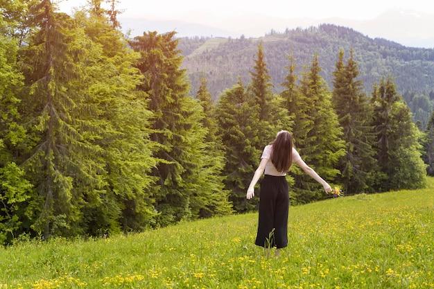 Młoda kobieta stoi na łące z bukietem kwiatów i szeroko otwartymi rękami