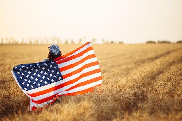 Młoda kobieta stoi na środku pola pszenicy z amerykańską flagą. pojęcie wolności. dzień niepodległości. 4 lipca.