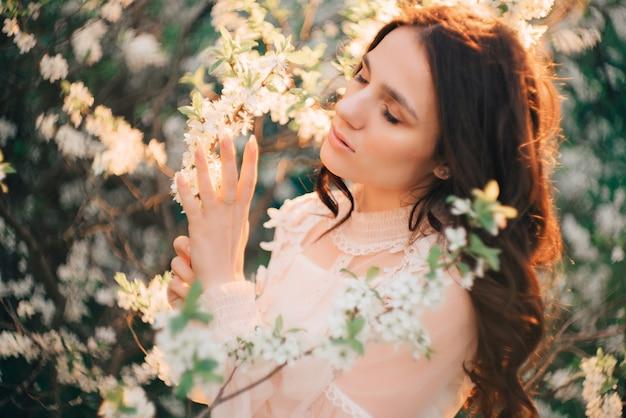 Młoda kobieta stoi na tle kwitnących drzew
