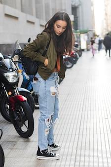 Młoda kobieta stoi na ulicy z plecakiem na ramieniu, patrząc na coś w kieszeni kurtki