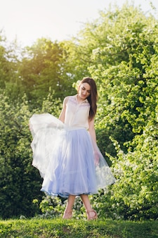 Młoda kobieta stoi na wzgórzu na tle kwitnących drzew