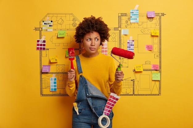 Młoda kobieta stoi obok szkic projektu domu gotowy do remontu