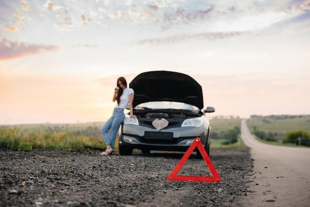 Młoda kobieta stoi obok zepsutego samochodu.
