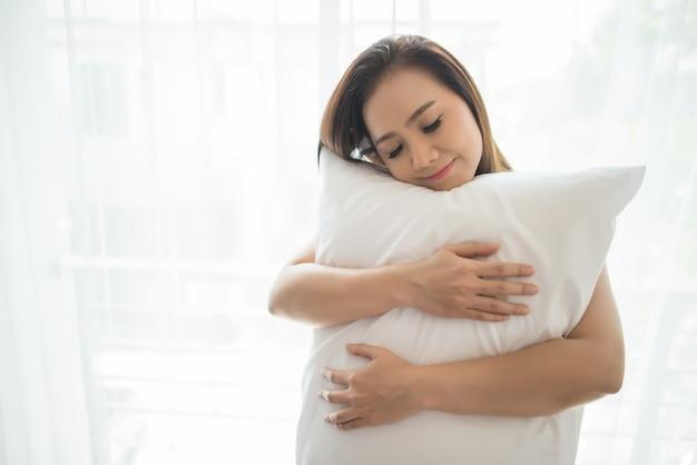 Młoda kobieta stoi obudzić się w sypialni