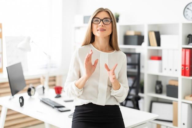 Młoda kobieta stoi, opierając się na stole w biurze.