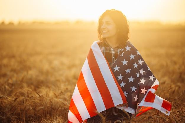 Młoda kobieta stoi owinięta amerykańską flagą na tle pięknego zachodu słońca. dzień niepodległości. 4 lipca. pojęcie wolności. ciepłe kolory. szczęśliwa dziewczyna z flagą w polu pszenicy.