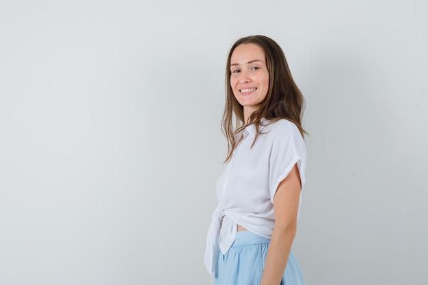 Młoda kobieta stoi prosto i pozuje z przodu w białej bluzce i jasnoniebieskiej spódnicy i wygląda wesoło