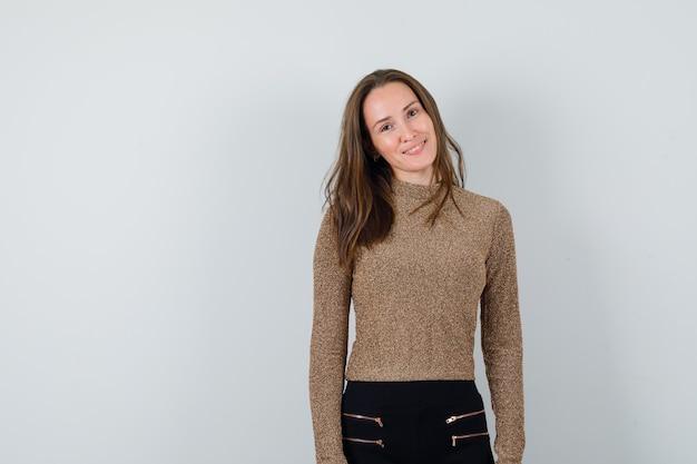 Młoda kobieta stoi prosto i uśmiecha się wdzięcznie w pozłacanym swetrze i czarnych spodniach i wygląda na szczęśliwą
