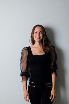 Młoda kobieta stoi prosto i uśmiecha się z wdziękiem w czarnej bluzce i czarnych spodniach i wygląda atrakcyjnie