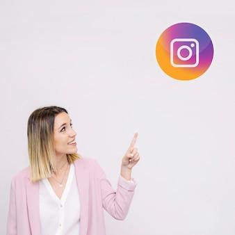 Młoda kobieta stoi przeciw białemu tłu wskazuje przy instagram logem