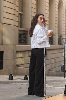 Młoda kobieta stoi przed budynkiem trzyma filiżankę kawy na wynos patrząc przez ramię