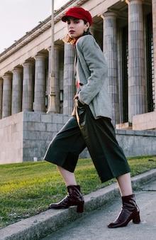 Młoda kobieta stoi przed budynkiem z rękami w kieszeni
