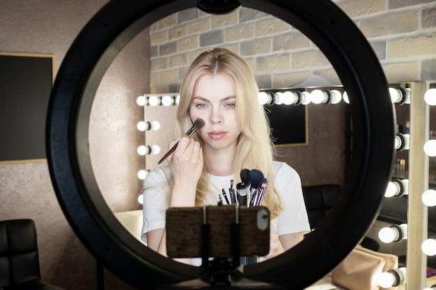 Młoda kobieta stoi przed pierścieniową lampą i prowadzi internetowe kursy makijażu