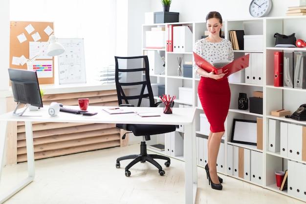 Młoda kobieta stoi w biurze i trzyma czerwony folder z dokumentami.
