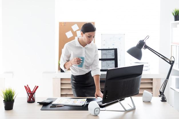 Młoda kobieta stoi w biurze, trzyma filiżankę i pisze na klawiaturze.