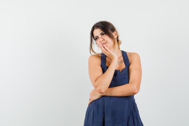 Młoda kobieta stoi w myślącej pozie w ciemnoniebieskiej sukience i wygląda na niezdecydowaną