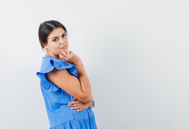 Młoda kobieta stoi w myślącej pozie w niebieskiej sukience i wygląda na pewną siebie