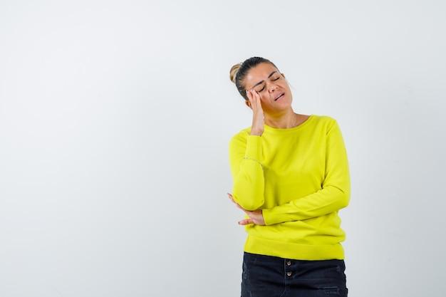 Młoda kobieta stoi w myślącej pozie w żółtym swetrze i czarnych spodniach i wygląda na zamyśloną