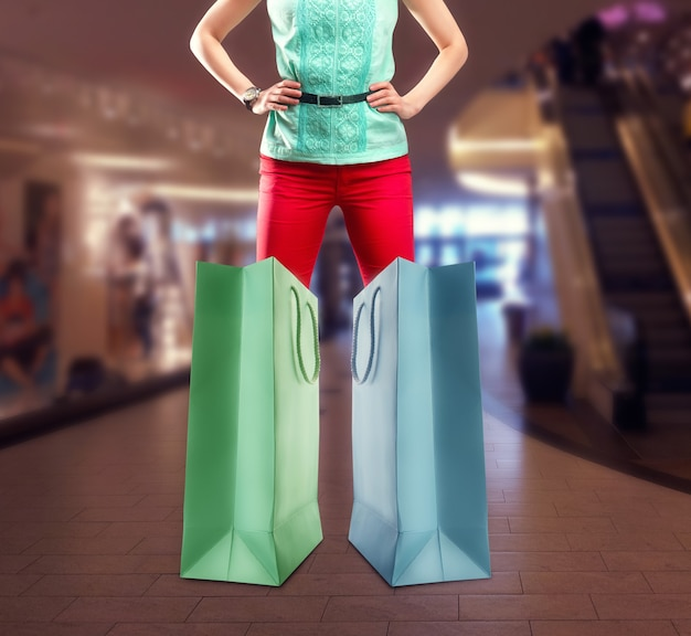 Młoda kobieta stoi w pobliżu dwóch dużych toreb na zakupy w centrum handlowym