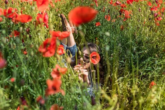 Młoda kobieta stoi w pobliżu kwitnącego pola maku. szczęśliwa dziewczyna na świeżym powietrzu, styl życia