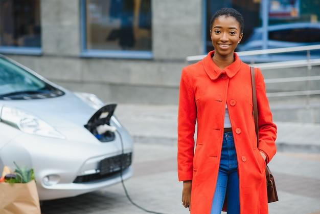 Młoda kobieta stoi w pobliżu samochodu elektrycznego i patrząc na kamery