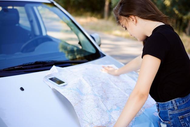 Młoda kobieta stoi w pobliżu samochodu i patrzy na mapę