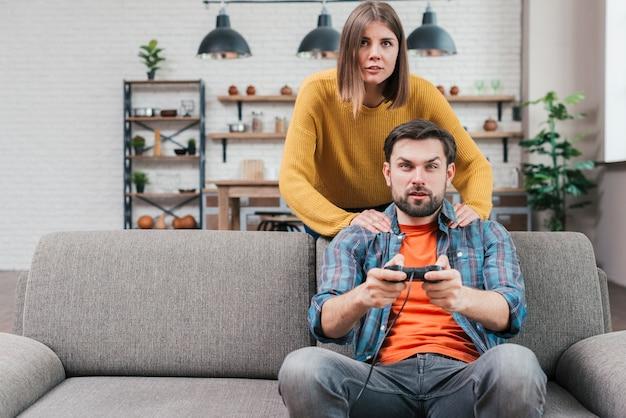 Młoda kobieta stoi za jej męża siedzi na kanapie grając w grę wideo