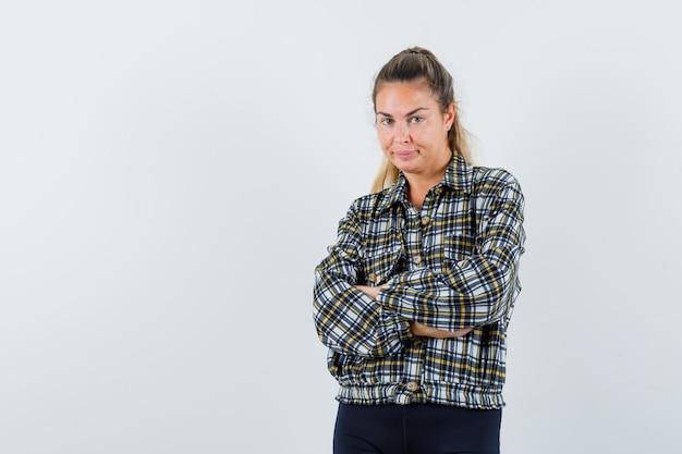 Młoda kobieta stoi ze skrzyżowanymi rękami w koszuli, spodenkach i wygląda pewnie. przedni widok.