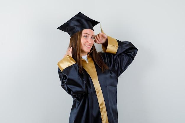 Młoda kobieta stojąc absolwentka pozując w akademickim stroju i patrząc radośnie, widok z przodu.