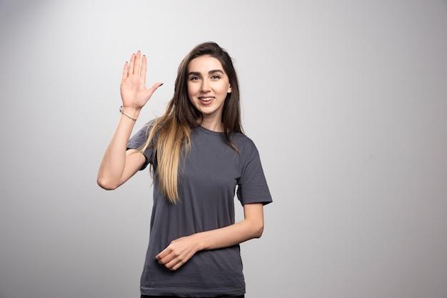 Młoda kobieta stojąc i pozowanie ręką