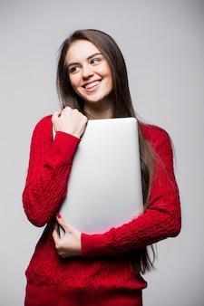 Młoda kobieta stojąc i trzymając laptop. szczęśliwa młoda dziewczyna za pomocą swojego laptopa, na białym tle na białej ścianie.