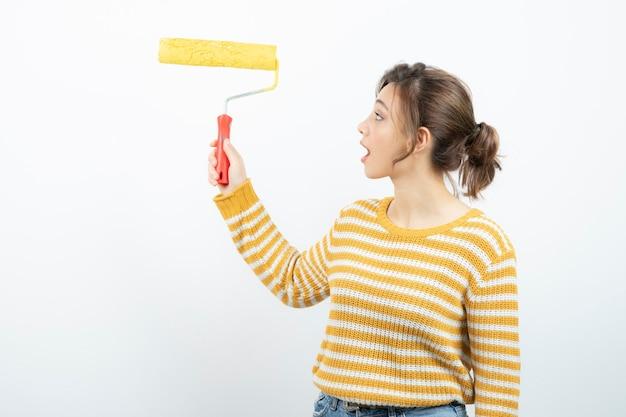 Młoda kobieta stojąc i trzymając w ręku wałek do malowania.