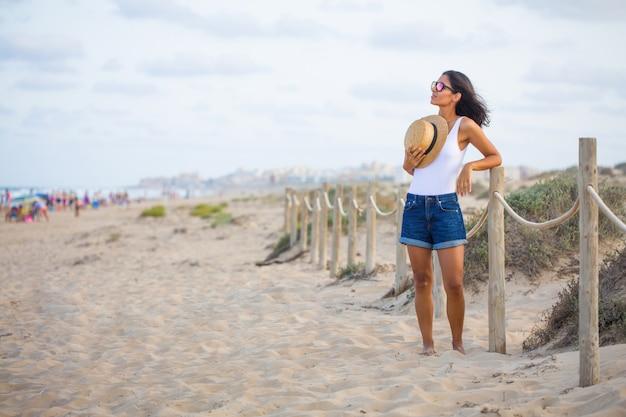 Młoda kobieta stojąc na plaży