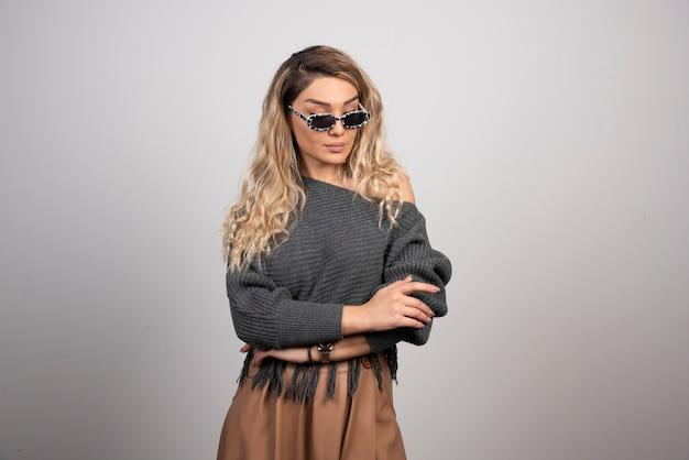 Młoda kobieta stojąc na szarym tle w okularach.