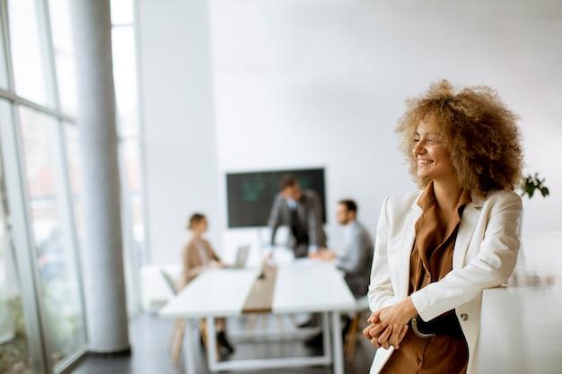 Młoda kobieta stojąc w nowoczesnym biurze