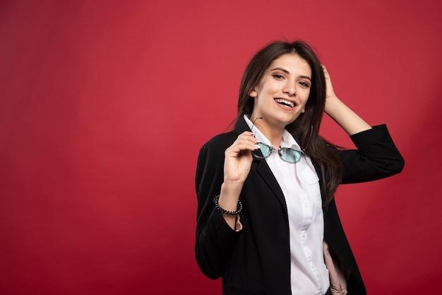 Młoda kobieta stojąc w okularach na czerwonym tle.