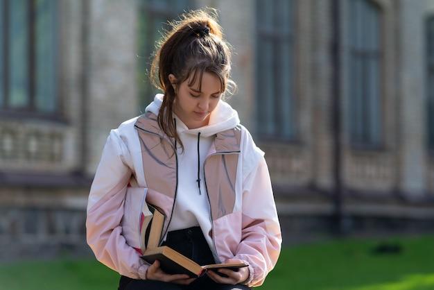 Młoda kobieta stojąca czytając książkę na zewnątrz
