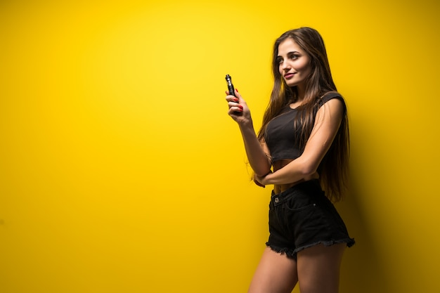 Młoda kobieta stojąca i vaping na żółtej ścianie.
